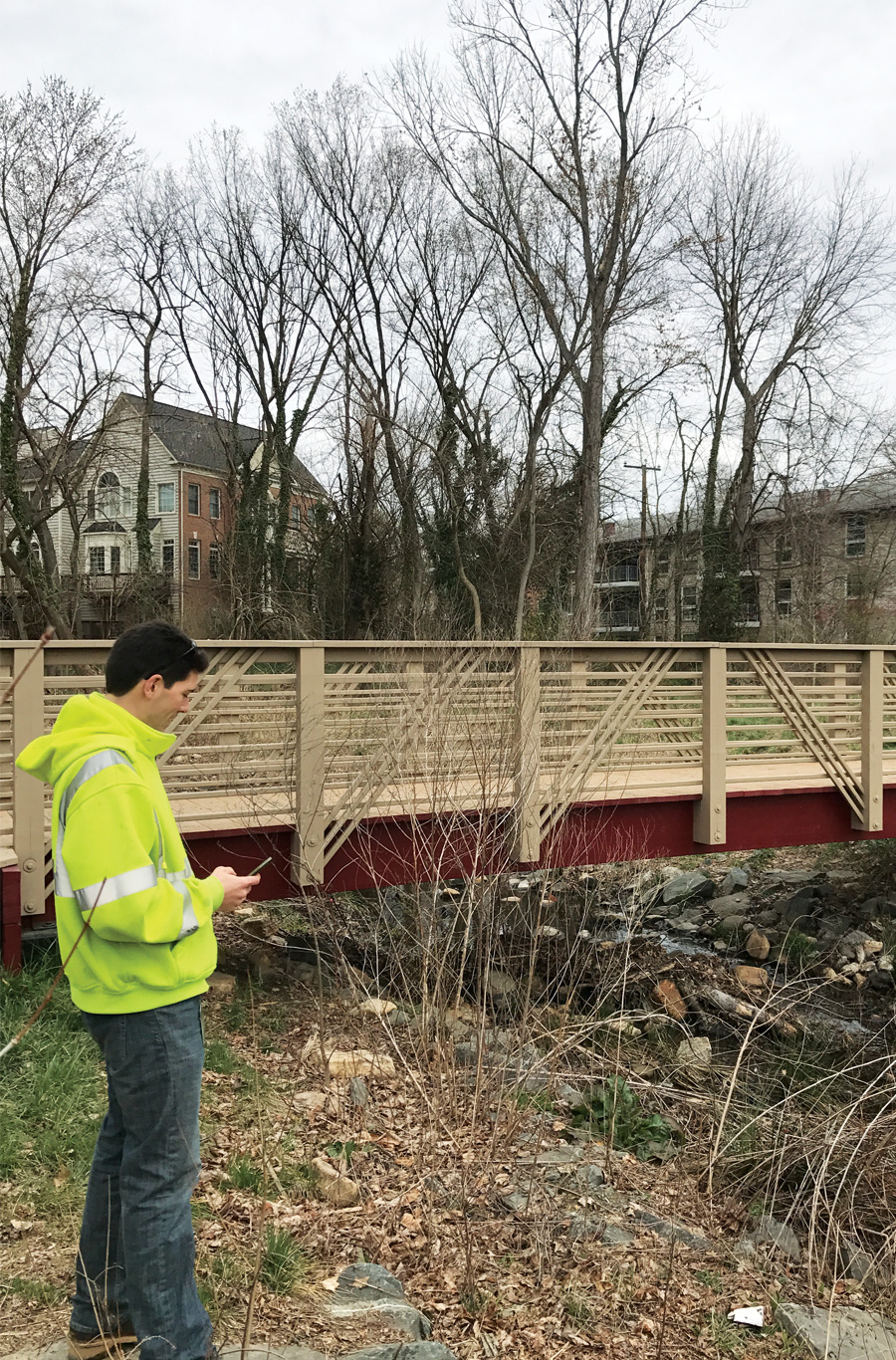 A city employee uses Collector for ArcGIS on a mobile device to obtain information about a bridge in Falls Church. (Photo courtesy of Andrew Peters.)