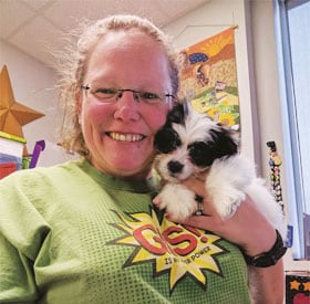 Kelly Adams wears her GIS shirt and gives the office therapy pup, a quick snuggle