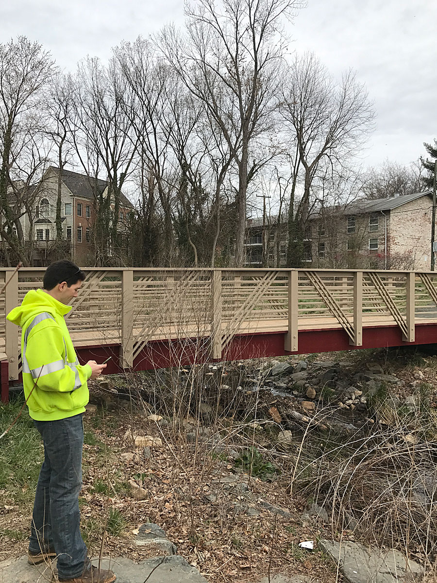 A city employee uses Collector for ArcGIS on a mobile device to collect information about a bridge in Falls Church. Photo by Andrew Peters.