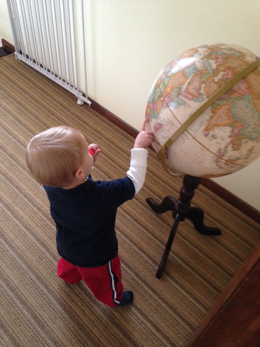 While brushing his teeth, Miller points to countries he has learned about on a globe.