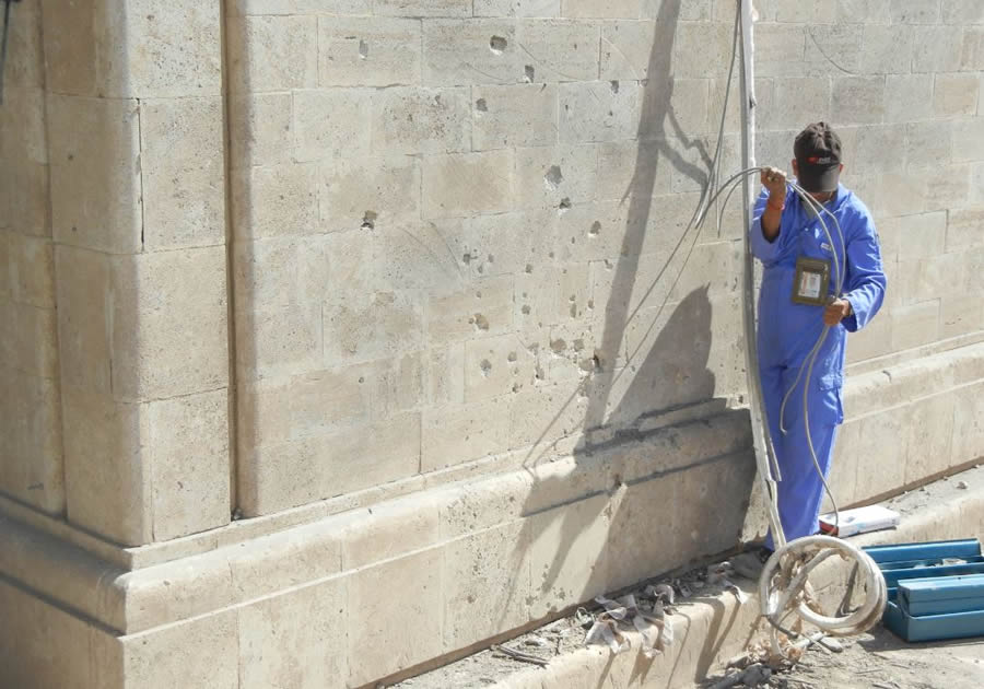 A worker starts to repair a building damaged by a rocket in the Green Zone in Baghdad, Iraq. Berry served in both Afghanistan and Iraq.