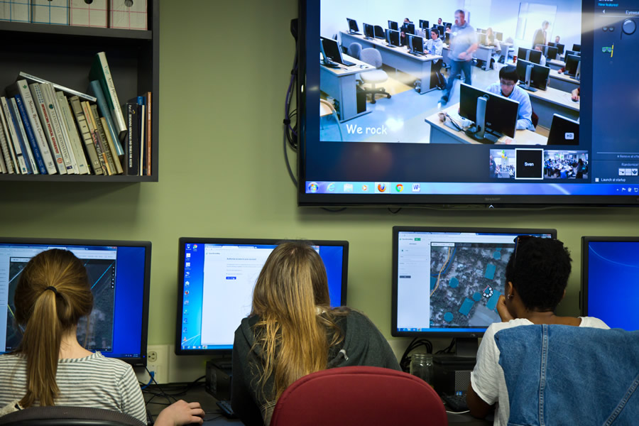 Several George Washington University students focus on creating their maps. A screen above them displays a live feed of their counterparts at George Mason University in Fairfax, Virginia, simultaneously mapping. Photo/Heather Blevins