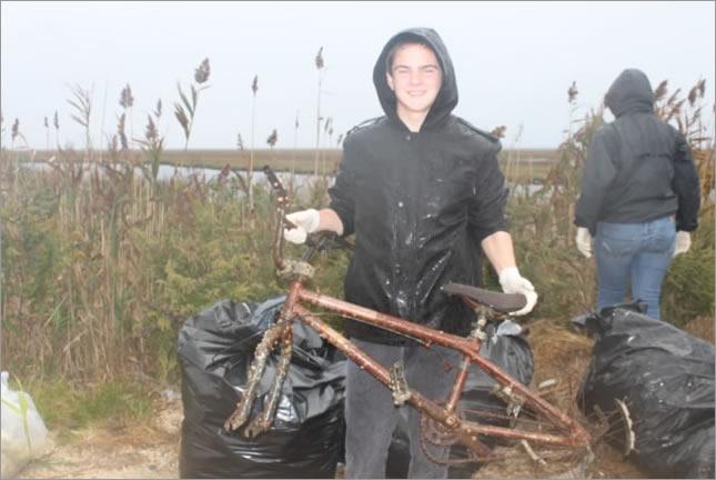 A volunteer picks up debris near a waterway in New Jersey.
