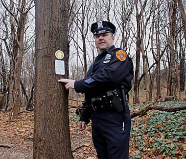 Officer James Garside of the Suffolk County Police Department spearheaded the drive to install the trail markers in Cold Spring Harbor State Park. Photo by Janee Law © Long Islander News. Used with permission.