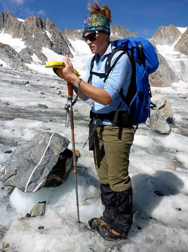GIST student Chelsea Cheney collects elevation data for use by the University of North Dakota for some of the university's research into glacial recession.