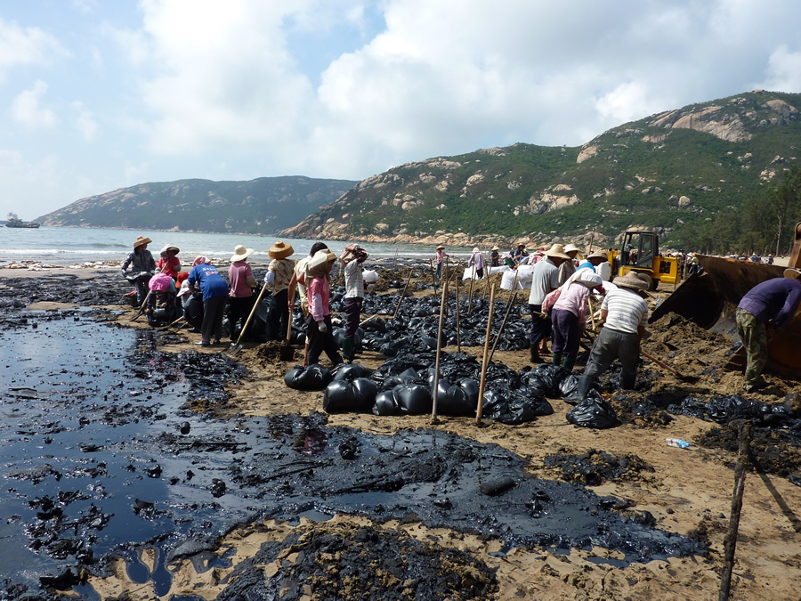 People clean the beaches in a China coastal community after an oil tanker spill.