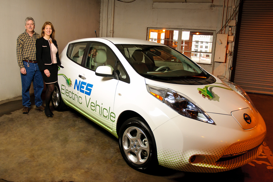 Carla Nelson and Keith Brown stand inside the NES garage with one of the electric utility's three Nissan Leaf vehicles, which were purchased as part of the market testing. Credit: Joe Weaver Photography.