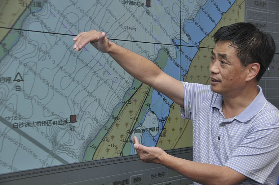 Staff member for the Changjiang Waterway Bureau reviewing nautical charts.