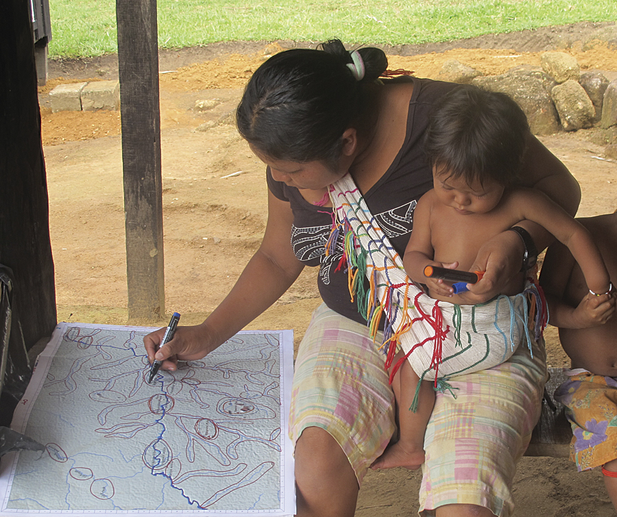 A village woman drawing polygons on an elevation map.