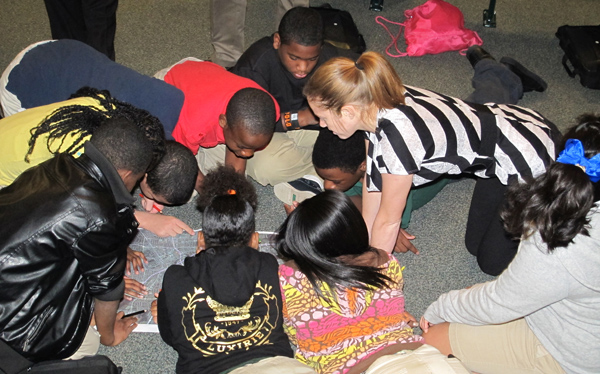 Molly Richardson ( right), an intern at the US Army Corps of Engineers Huntsville Center, helps sixth graders at Ed White Middle School in Huntsville, Alabama, with a GIS activity. The school was among six schools in Alabama that observed GIS Day. (Photo by Jo Anita Miley)