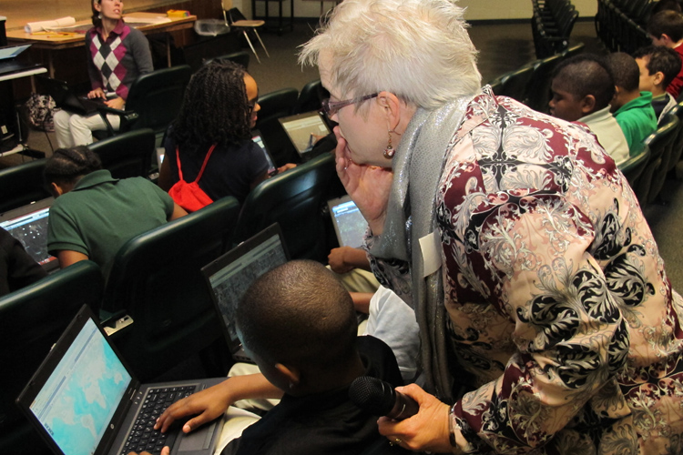 Beverly Richey, a geographer and GIS specialist from the US Army Corps of Engineers Huntsville Center, helps a sixth grader at Ed White Middle School work with an online map.