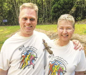 Kathryn Scott and Brian Hall, GIS analysts let a leaf-tailed gecko walk over their Esri t-shirts