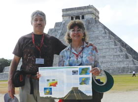 Laura Hall and Bill Di Paolo hold up an article in front of a Mayan pyramid