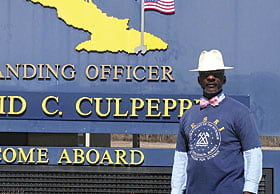Dr. Lemuel Patterson, a STEM education instructional systems specialist poses at the welcome sign to Guantanamo Bay