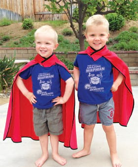 Three year old twins wear GIS T-shirts and capes