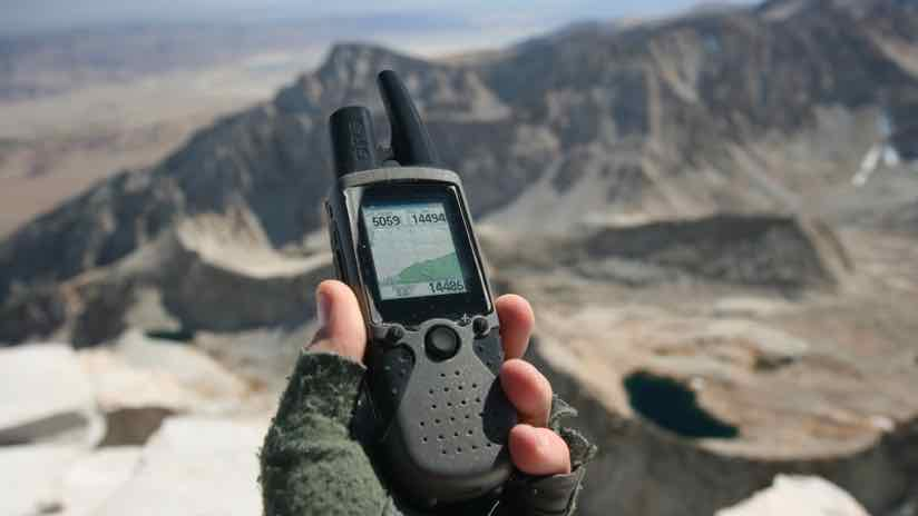 handheld GPS receiver in a mountain landscape
