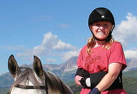 Lara Oles, GIS training specialist wears her Map Girl T-shirt while posing on her horse
