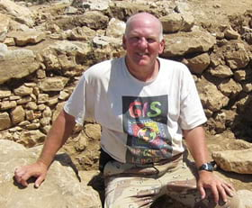 Tom Miller, GIS manager is posing with an olive press stone found at the Khirbet el-Maqatir archaeological dig in the West Bank of Israel