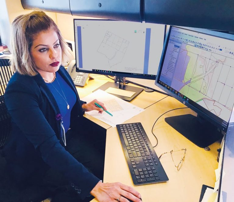 An analyst using GIS on a computer