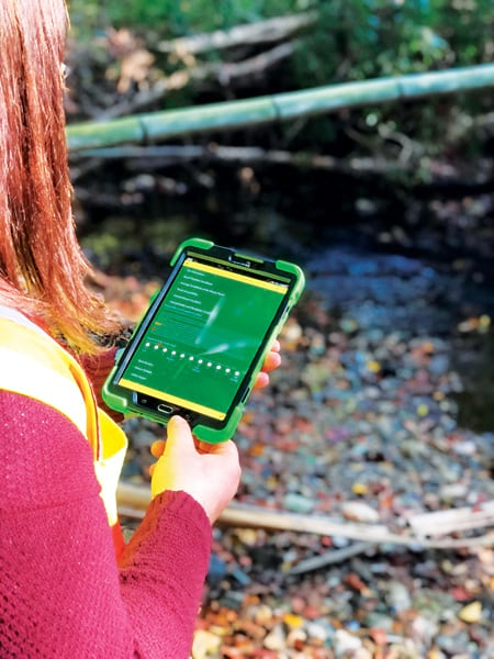 A photo of a woman using Survey123 for ArcGIS on a tablet