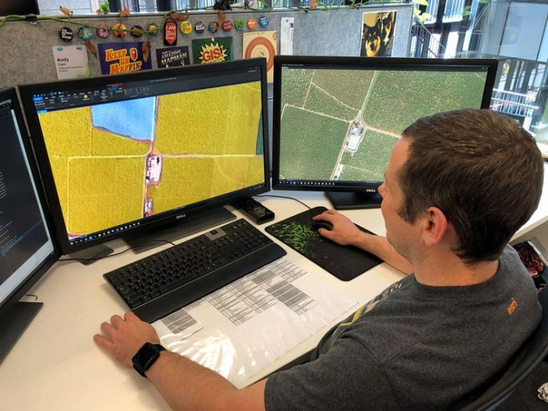 A man looking at aerial imagery on two computer screens