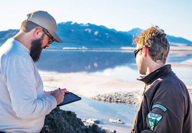 A photo of two BLM staff members using a mobile device near a lake