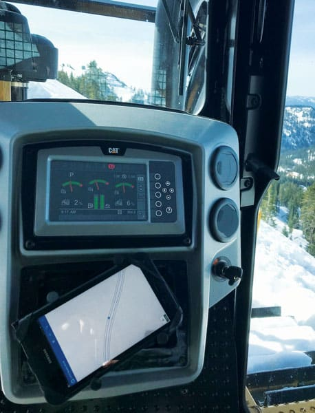 A photo from inside a bulldozer, showing the Collector for ArcGIS map on a tablet under the dashboard and piles of snow outside