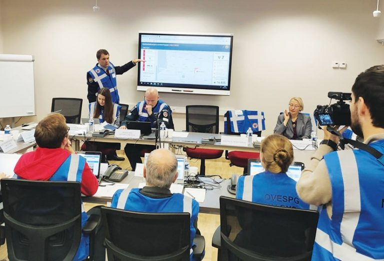 A photo of officials in a room looking at a screen during the exercise