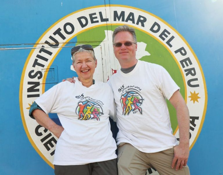 A man and a woman wearing Esri T-shirts stand next to each other in front of a sign