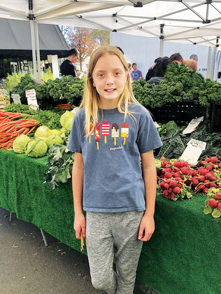 A girl wearing an Esri T-shirt posing in front of a vegetable stand