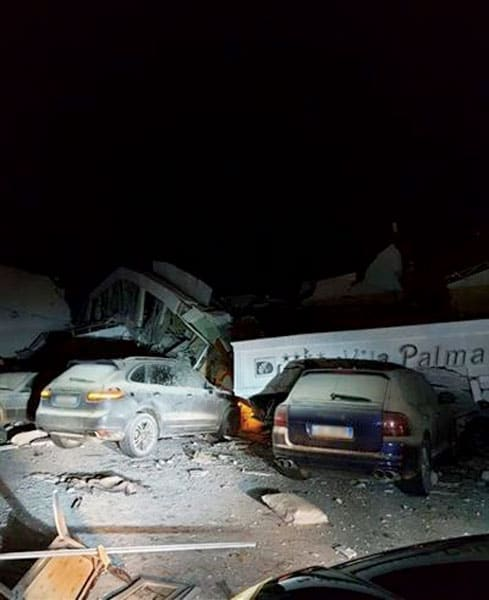 Photo of two cars destroyed by a fallen building