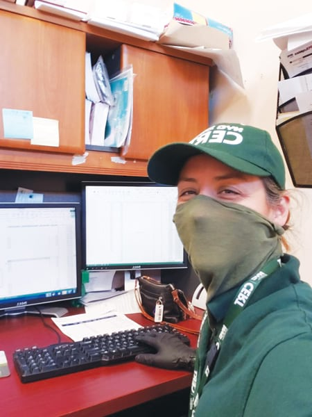 A photo of Terese Flores sitting at a computer wearing a green mask that matched her green CERT hat and shirt