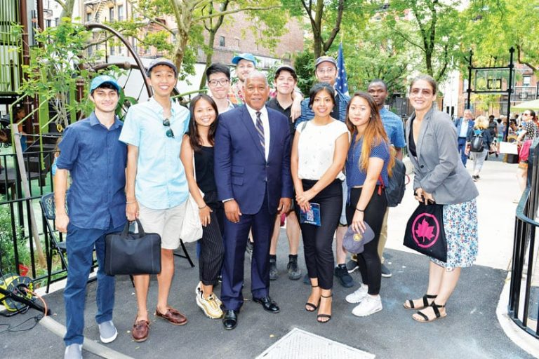 A photo of ten college-age interns standing in a park with Terese Flores and NYC Parks commissioner Mitchell J. Silver