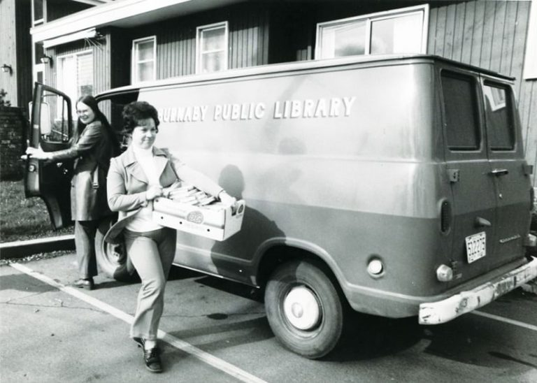 An old, black-and-white photo of a woman carrying a crate of books next to a van labeled Burnaby Public Library