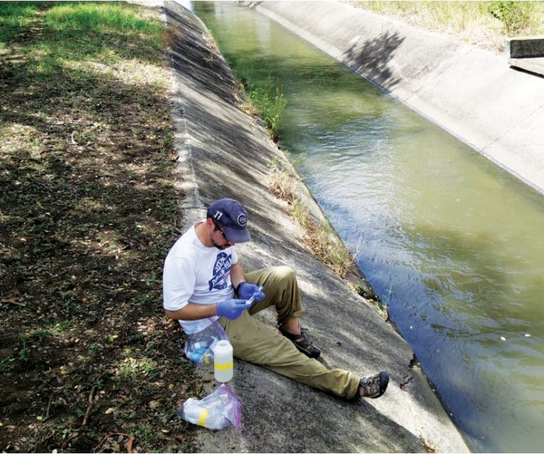 A photo of a man sitting on the side of a wash using some scientific fieldwork instruments