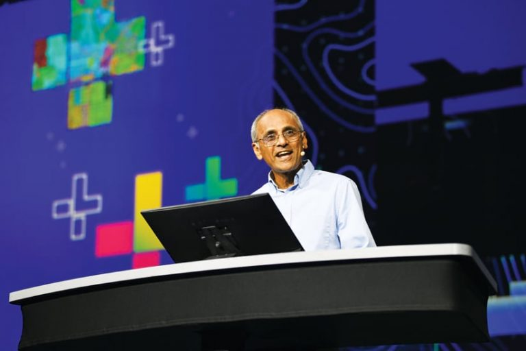 A photo of Sud Menon talking into a microphone, giving a demonstration onstage, at a computer