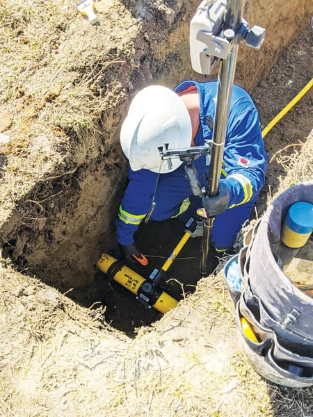 A photo of a fieldworker in a blue suit and a hardhat taking a bar code measurement of an underground asset that has yet to be buried