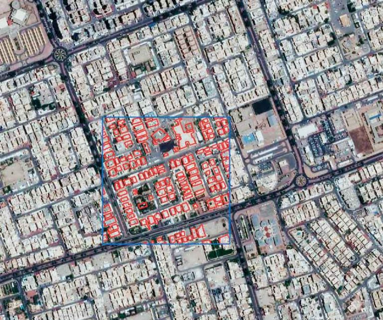 Satellite imagery of a neighborhood in Kuwait city with one area surrounded by a square blue line and the buildings within that square outlined with red lines
