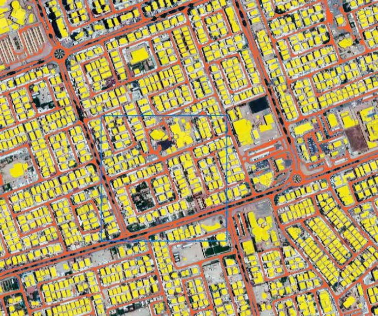 Satellite imagery of a neighborhood in Kuwait City with the streets marked by red lines and the building footprints denoted in yellow