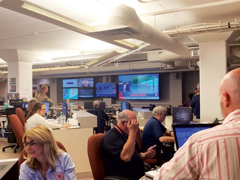 People in the State Emergency Operations Center looking at computers and various electronic displays that show dashboards, news, and maps