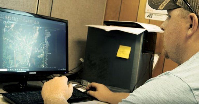 Man in a baseball cap working on a desktop computer