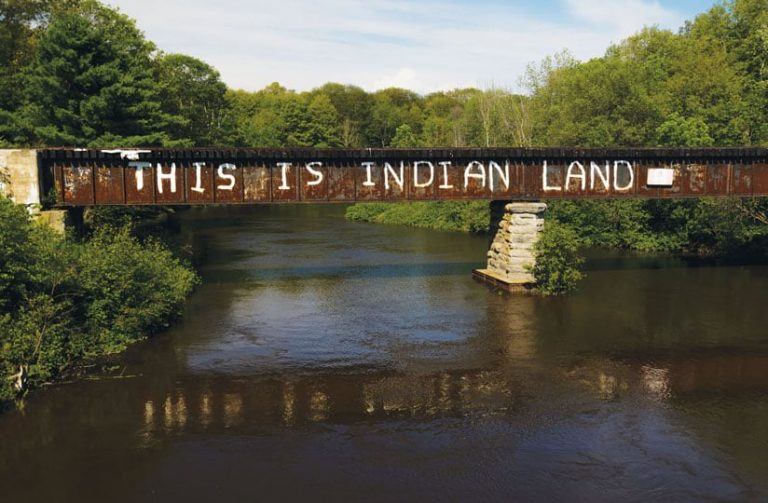 """A train bridge crossing the Garden River FirNation reserve with """"This is Indian Land"""" graffitied on the side"""