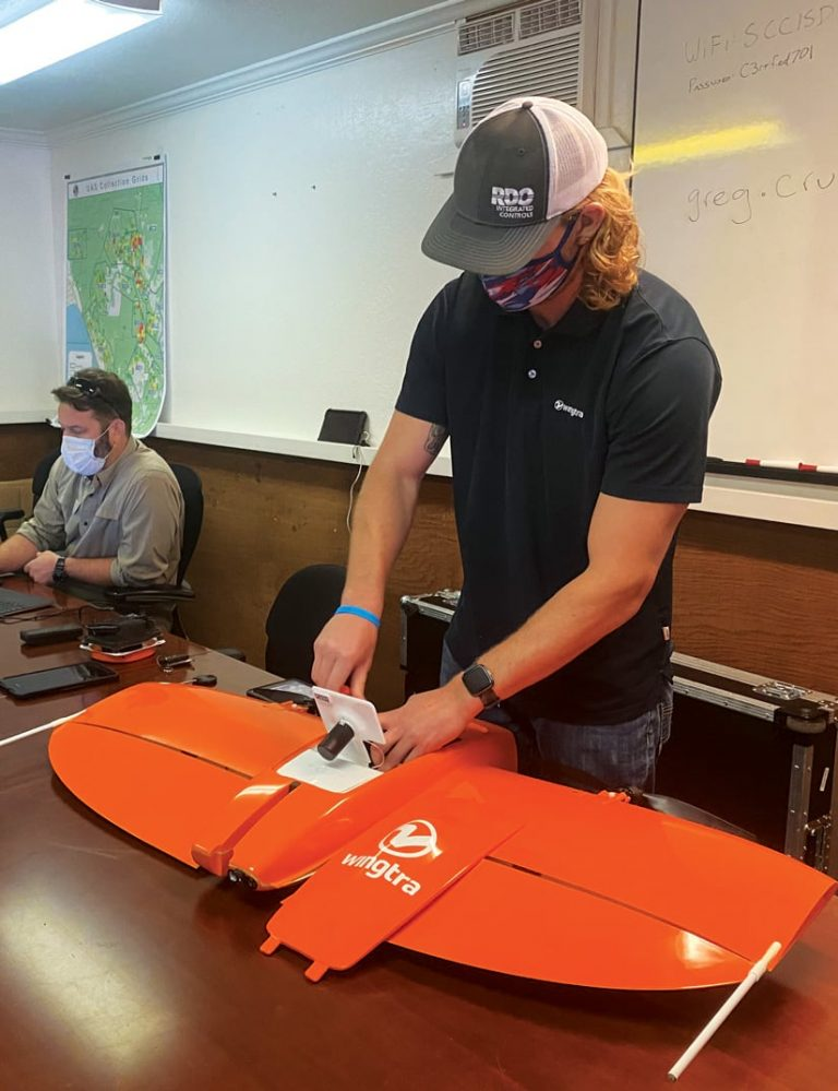 A person with a face mask and baseball cap builds an orange drone in an office