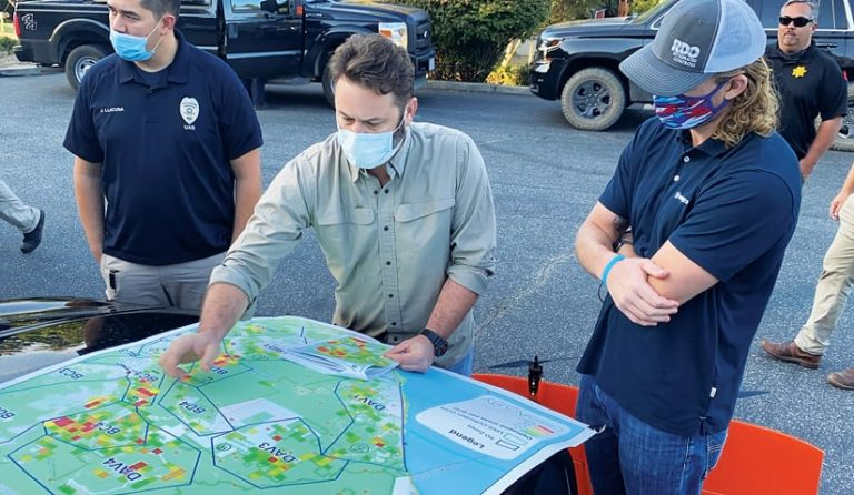 Three people wearing face maskslook at a map and one person points to a location on the map