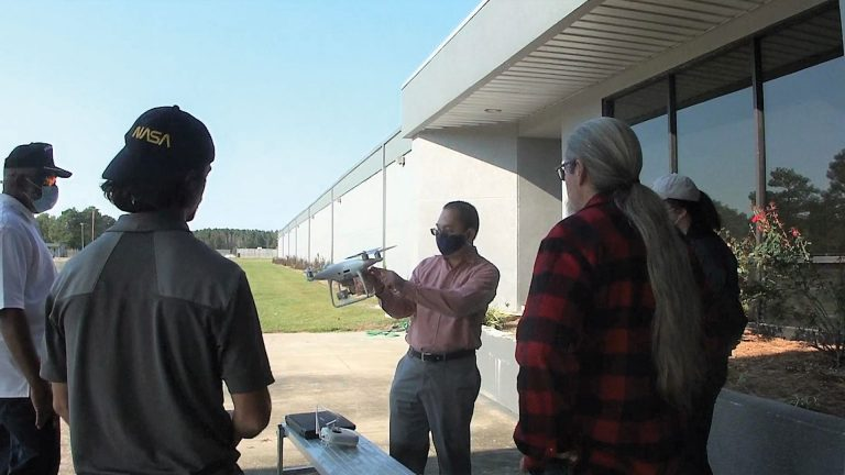 Dr. AdegokeAdemiluyi showing students a white UAV outside of a building