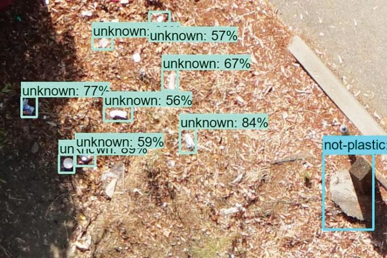 """Trash items detected in a land fill and marked by machine-learning with a turquoise rectangle stating """"unknown"""" with a percentage"""