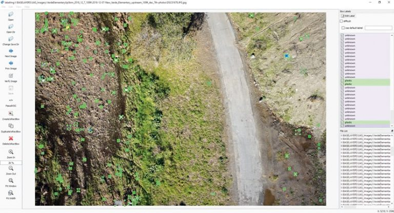 Drone imagery of a road, grass, and dirt, and green markers indicating where trash is located