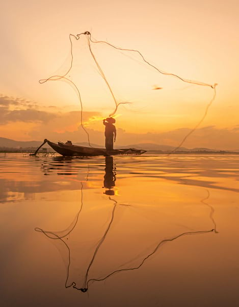 A silhouette of a fisherman in a boat on a freshwater water river at sunset