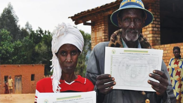 Two Rwandans holding up titles and certifications of land