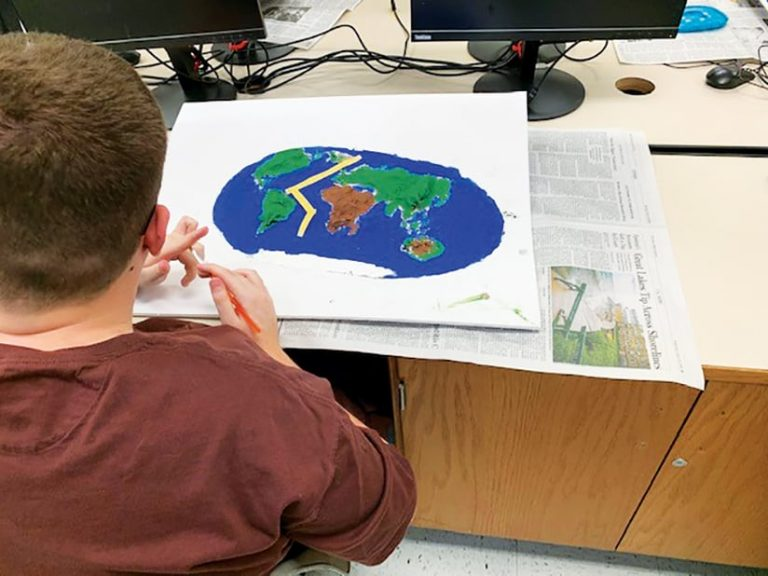 Student sitting at a desk working on a physical 3D map